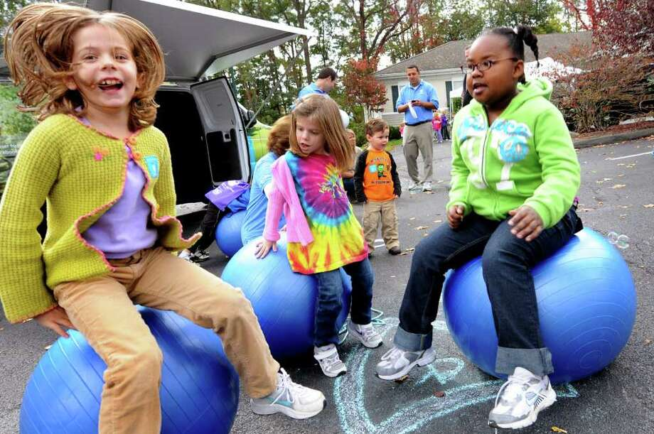 Katie Taylor, 7, left, her sister Alexander, 4, center, and friend Maya Meadows, 7, all of Albany bounce on balls during the Start Smart Festivalon Saturday, Oct. 15, 2011, at Addictions Care Center of Albany in Albany, N.Y. Katie and Maya both won awards in the poster contest, one of the events sponsored by BlueShield of Northeastern New York. (Cindy Schultz / Times Union) Photo: Cindy Schultz / 00014978A