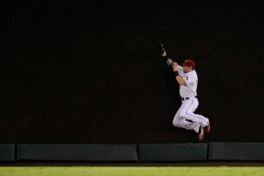ARLINGTON, TX - OCTOBER 15:  Josh Hamilton #32 of the Texas Rangers makes a catch at the wall to end the top of the fifth inning of Game Six of the American League Championship Series against the Detroit Tigers at Rangers Ballpark in Arlington on October 15, 2011 in Arlington, Texas. Photo: Kevork Djansezian, Getty / 2011 Getty Images