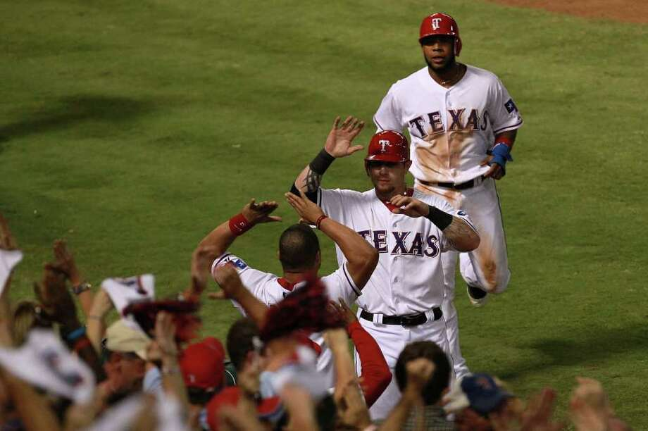 ARLINGTON, TX - OCTOBER 15:  Josh Hamilton #32 and Elvis Andrus #1 of the Texas Rangers jog to the dugout after scoring in the third inning to tie Game Six of the American League Championship Series 2-2 at Rangers Ballpark in Arlington on October 15, 2011 in Arlington, Texas. Photo: Ronald Martinez, Getty / 2011 Getty Images