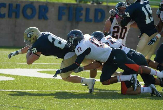 UC Davis player, #20, Colton Silveria dives for a touchdown as he drags UTSA player, #17, Erik Brown and UTSA player, #53, Brandon Reeves as the UC Davis Aggies hosts the University of Texas at San Antonio Roadrunners, Saturday Oct. 15, 2011. Brian Baer/Special to the San Antonio Express-News Photo: Brian Baer, Express-News / © 2011 Brian Baer