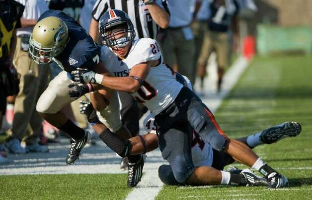 UTSA player, #20, Mauricio Sanchez  loses his helmet as he tackles UC Davis player, #7, Austin Edmonson during second half action, as the UC Davis Aggies 38-17 victory over the University of Texas at San Antonio Roadrunners, Saturday Oct. 15, 2011. Brian Baer/Special to the San Antonio Express-News Photo: Brian Baer, Express-News / © 2011 Brian Baer