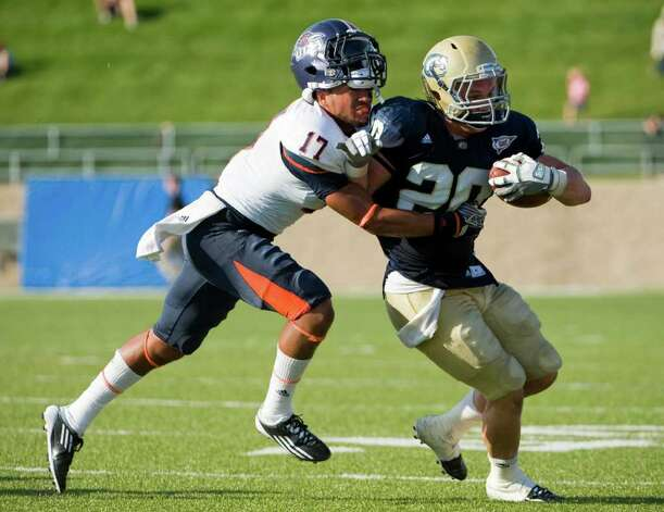 UTSA's Erik Brown  (left) loses his hemet as he tackles UC Davis' Colton Silveria on Oct. 15, 2011. Brian Baer/Special to the San Antonio Express-News Photo: Brian Baer, Express-News / © 2011 Brian Baer
