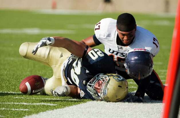 UTSA player, #17, Erik Brown  loses his hemet as he tackles UC Davis player, #20, Colton Silveria during second half action, as the UC Davis Aggies 38-17 victory over the University of Texas at San Antonio Roadrunners, Saturday Oct. 15, 2011. Brian Baer/Special to the San Antonio Express-News Photo: Brian Baer, Express-News / © 2011 Brian Baer