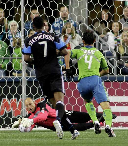Seattle Sounders FC goalkeeper Kasey Keller makes a stop as Sounders' Patrick Ianni, and San Jose Ea