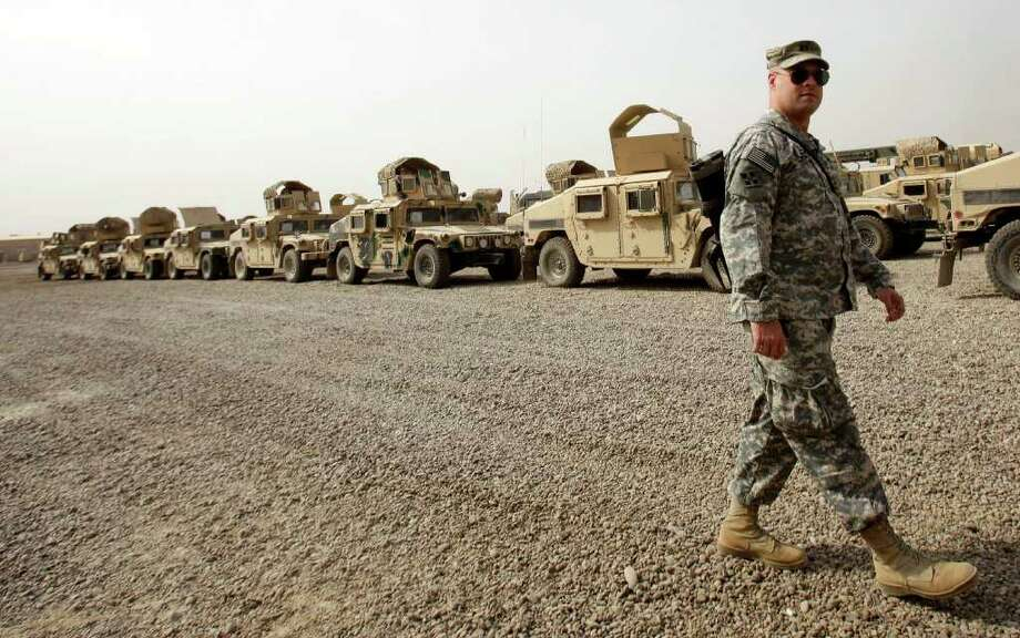 A U.S. army soldier walks past military Humvees which are ready to be shipped out of Iraq at a staging yard at Camp Sather, part of the sprawling U.S. military Victory Base Complex that is set to close in Baghdad, Iraq, Saturday, Oct. 15, 2011. The U.S. has promised to withdraw from Iraq by the end of the year as required by a 2008 security agreement between Washington and Baghdad. Some 41,000 U.S. troops are scheduled to clear out along with their equipment. It's still unclear if the U.S. military will keep several thousand troops in Iraq as leaders weigh whether staunch political opposition in both nations is worth the risk. The uncertainty has been a logistical nightmare for American commanders, who could be asked at the last minute to keep some equipment and manpower back but for now must push ahead in case the withdrawal plan stands. (AP Photo/Khalid Mohammed) Photo: Khalid Mohammed / AP