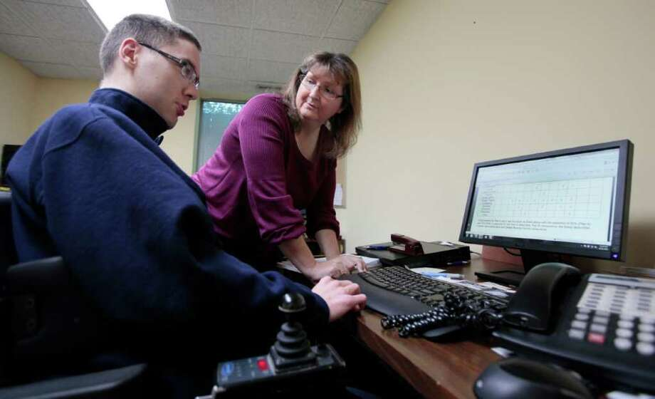 "ADVANCE FOR SUNDAY OCT. 16, 2011 - In this Oct. 11, 2011 photo, Leigh Ann Stephens, executive director of DuPage Center for Independent Living, talks with Chris Ludwig, youth services coordinator for the center in Glen Ellyn, Ill. Stephens wrote a letter in August ""asking, pleading"" for $50,000 the state owed to the DuPage Center for Independent Living. It was the third time in two years that she had sent a hardship letter warning the center, which helps people with disabilities live outside of costly nursing homes, would close if it wasn't paid. (AP Photo/Kiichiro Sato) Photo: Kiichiro Sato"