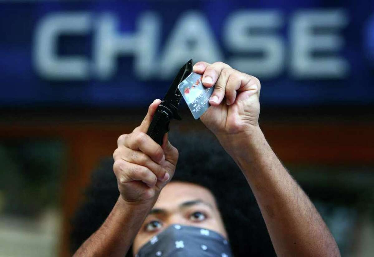 A protester cuts up a bank card during the