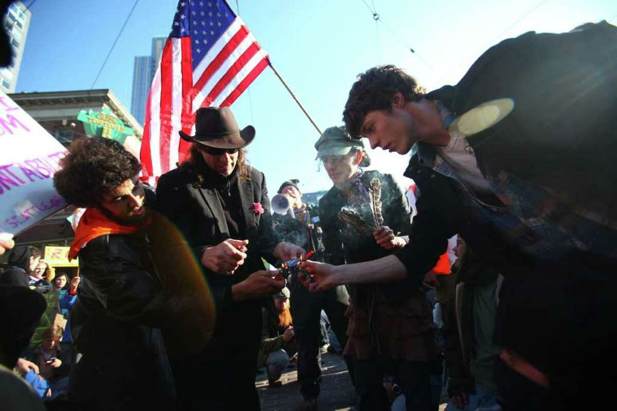 Occupy Seattle protesters burn credit and debit cards in front of Pike Place Market.