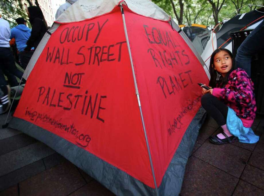 Leyla Bevis-Mast writes on her family's tent in Westlake Park in Seattle. The tents were erected in defiance of the city, which has a no camping rule in the park. Photo: JOSHUA TRUJILLO / SEATTLEPI.COM