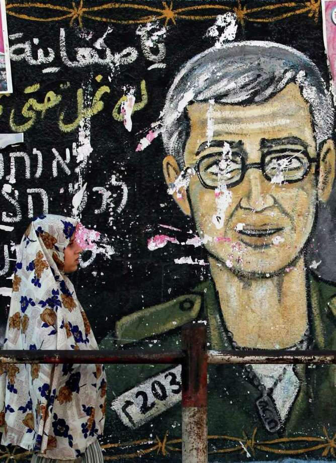 A Palestinian woman walks in front of a wall painting depicting Israeli soldier Gilad Schalit, who is being held in Gaza since he was captured by Hamas-allied militants in a cross-border raid in 2006, in Jebaliya, northern Gaza Strip, Saturday, Oct. 15, 2011. Hamas officials were hashing out a strategy with Egyptian intelligence officers Saturday how to transfer an Israeli soldier they have held captive for the past five years to Israel, a senior Hamas official said.(AP Photo/Hatem Moussa) Photo: Hatem Moussa / AP