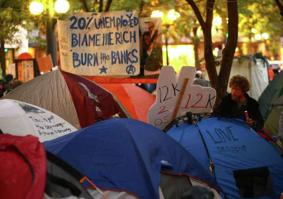 An Occupy Seattle protester writes on his tent in Westlake Park. Photo: JOSHUA TRUJILLO / SEATTLEPI.COM