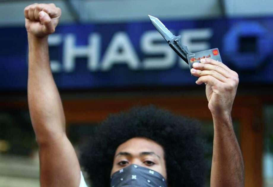 A protester prepares to cut up a bank card during the Occupy Seattle protest in front of Chase Bank on 4th Avenue. Photo: JOSHUA TRUJILLO / SEATTLEPI.COM