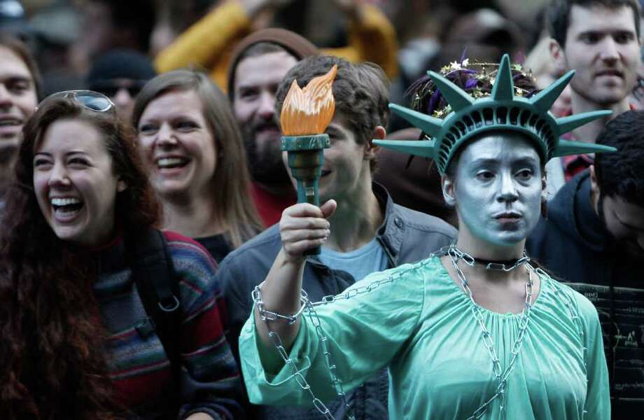 Occupy Seattle protester Aarianna Morada, dressed as Lady Liberty, stands with others at the Occupy Seattle rally in downtown Seattle. Photo: JOE DYER / SEATTLEPI.COM