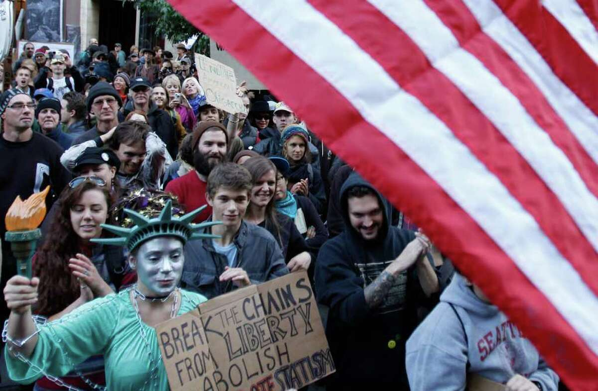 A woman is dressed as Lady Liberty at an Occupy Seattle rally in downtown Seattle near the Westlake Center on Saturday, Oct. 15, 2011.