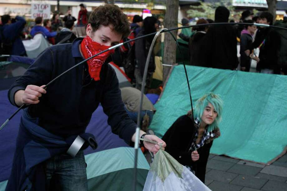 People set up tents in solidarity with protesters in Wall St. at an Occupy Seattle rally in downtown Seattle at Westlake park on Saturday, Oct. 15, 2011 Photo: JOE DYER / SEATTLEPI.COM