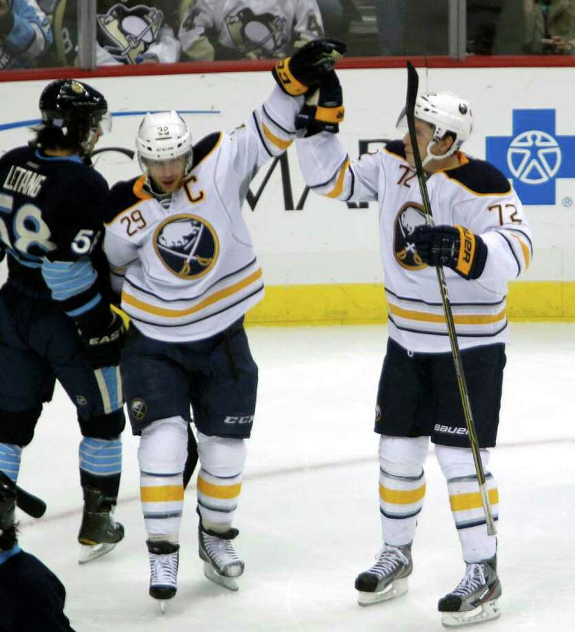 Buffalo Sabres' Luke Adam (72) celebrates his goal with teammate Jason Pominville as Pittsburgh Penguins' Kris Letang skates by in the first period of an NHL hockey game on Saturday, Oct. 15, 2011, in Pittsburgh. (AP Photo/Keith Srakocic) Photo: Keith Srakocic