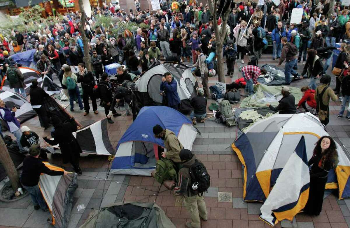 People set up tents in solidarity with protesters in Wall St. at an Occupy Seattle rally in downtown Seattle at Westlake park on Saturday, Oct. 15, 2011
