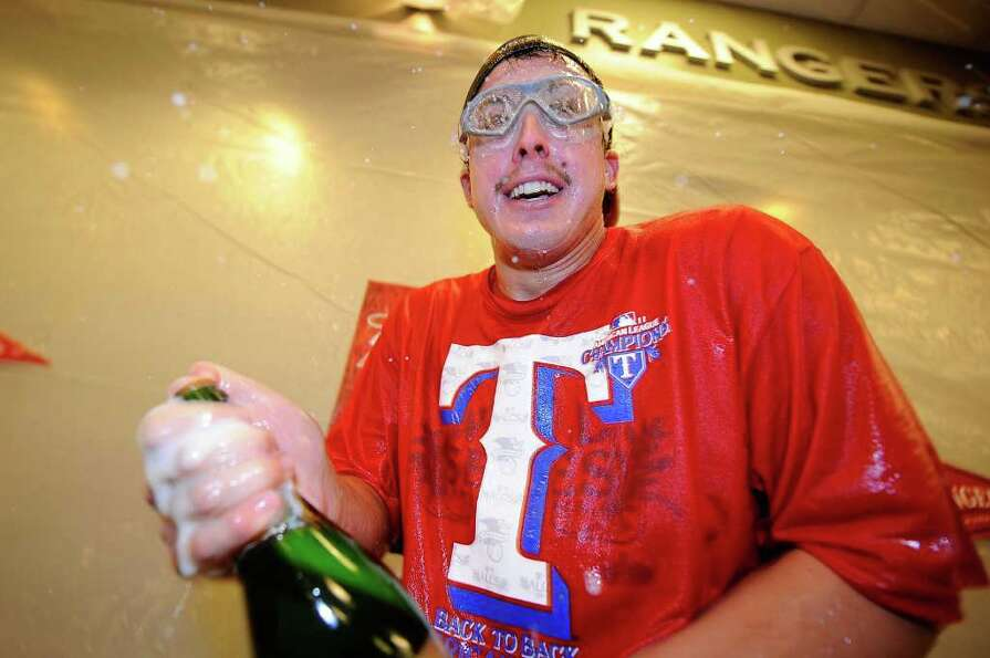 ARLINGTON, TX - OCTOBER 15:  Derek Holland #45 of the Texas Rangers celebrates in the clubhouse afte