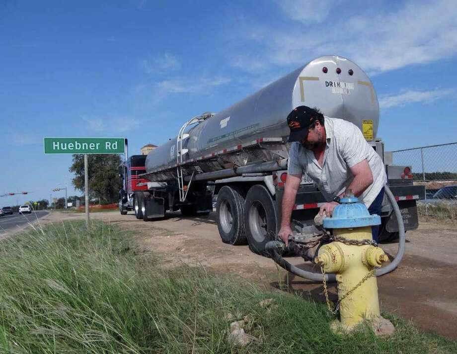 Buddy Dixon fills his tanker truck with water from a hydrant near the intersection of Loop 1604 at Huebner Road on Friday, Sept. 30, 2011. The water will be delivered on behalf of BexarMet to the Anaqua Springs Ranch development for use by residents. Photo: BILLY CALZADA, Billy Calzada/gcalzada@express-news.net / gcalzada@express-news.net