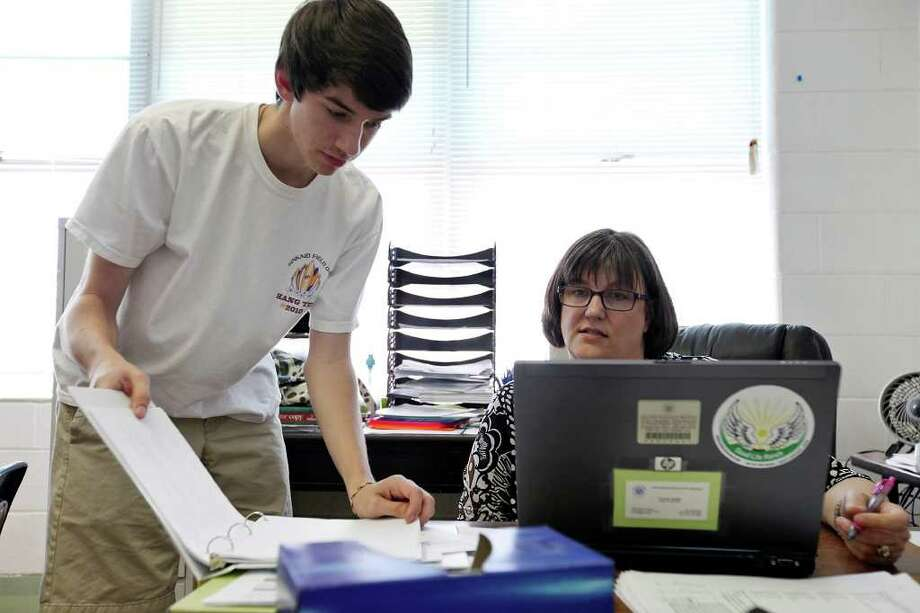 Sophomore  Hayden Wood, 15, (left) checks his grades on a laptop with teacher Laurie Smith during his English II class Oct. 13 at the International School of the Americas. North East ISD suggests $64 million in technology upgrades districtwide as part of its $399.4 million bond proposal. Photo: EDWARD A. ORNELAS, EDWARD A. ORNELAS/eaornelas@express-news.net / © SAN ANTONIO EXPRESS-NEWS (NFS)