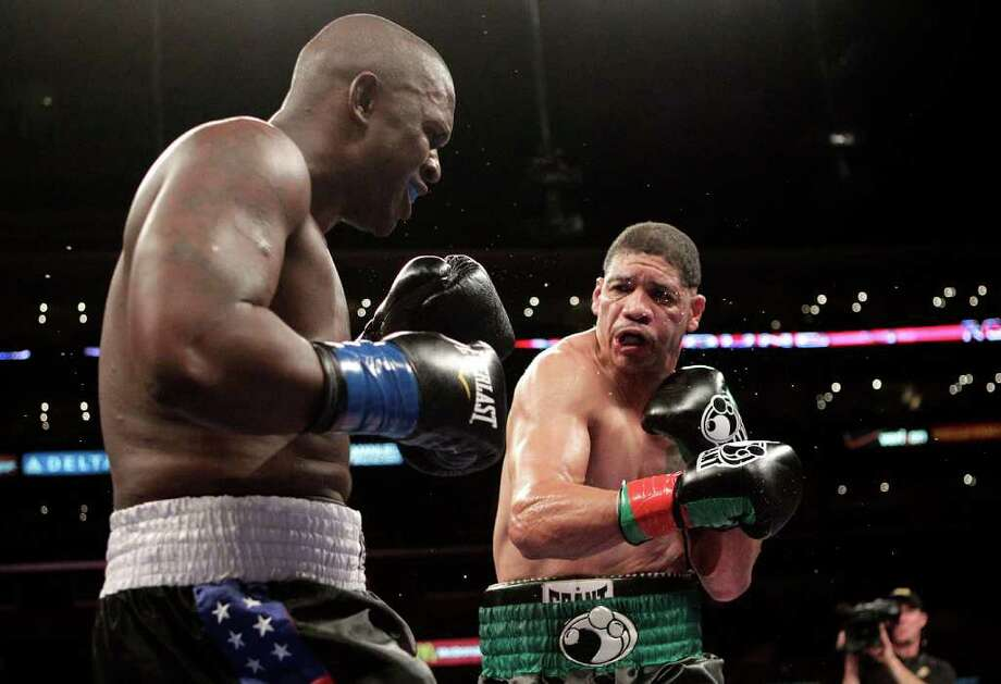 Dewey Bozella, right, lands a punch to the face of Larry Hopkins in the fourth round of a boxing match in Los Angeles, Saturday, Oct. 15, 2011. Bozella won by unanimous decision after the fourth round. (AP Photo/Jae Hong) Photo: Jae Hong