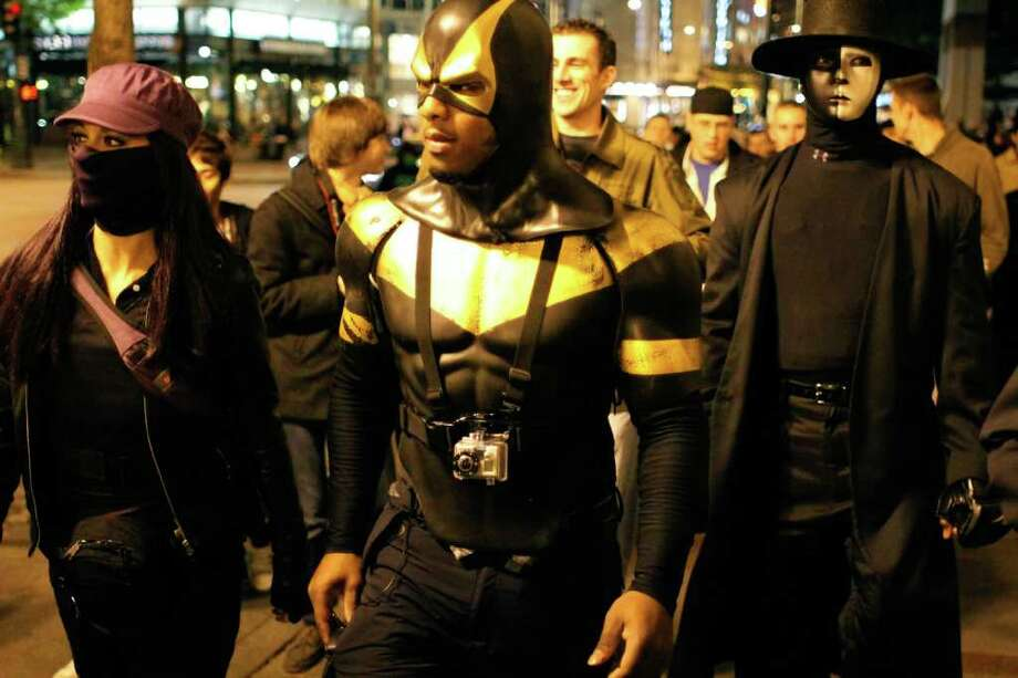 "Phoenix Jones and his posse of Seattle super heroes make an appearance at the Occupy Seattle protests at Westlake Park.  Phoenix Jones said that he understands why they are protesting, but added, ""Getting arrested sucks. Beleive me I know."" On Saturday, Oct. 15, 2011 in Seattle Photo: JOE DYER / SEATTLEPI.COM"