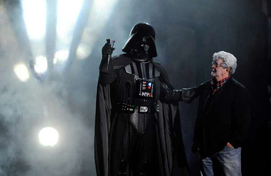 """""""Darth Vader"""" accepts the Ultimate Villain award from """"Star Wars"""" creator George Lucas during the 2011 Scream Awards, Saturday, Oct. 15, 2011, in Los Angeles. The award show is dedicated to the horror, science fiction and fantasy genres of feature films, television and comic books. (AP Photo/Chris Pizzello) Photo: Chris Pizzello"""
