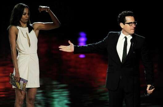 """""""Super 8"""" director J.J. Abrams, right, gestures to presenter Zoe Saldana as he accepts the Best Sci-Fi Movie award at the 2011 Scream Awards, Saturday, Oct. 15, 2011, in Los Angeles. The award show is dedicated to the horror, science fiction and fantasy genres of feature films, television and comic books. (AP Photo/Chris Pizzello) Photo: Chris Pizzello"""