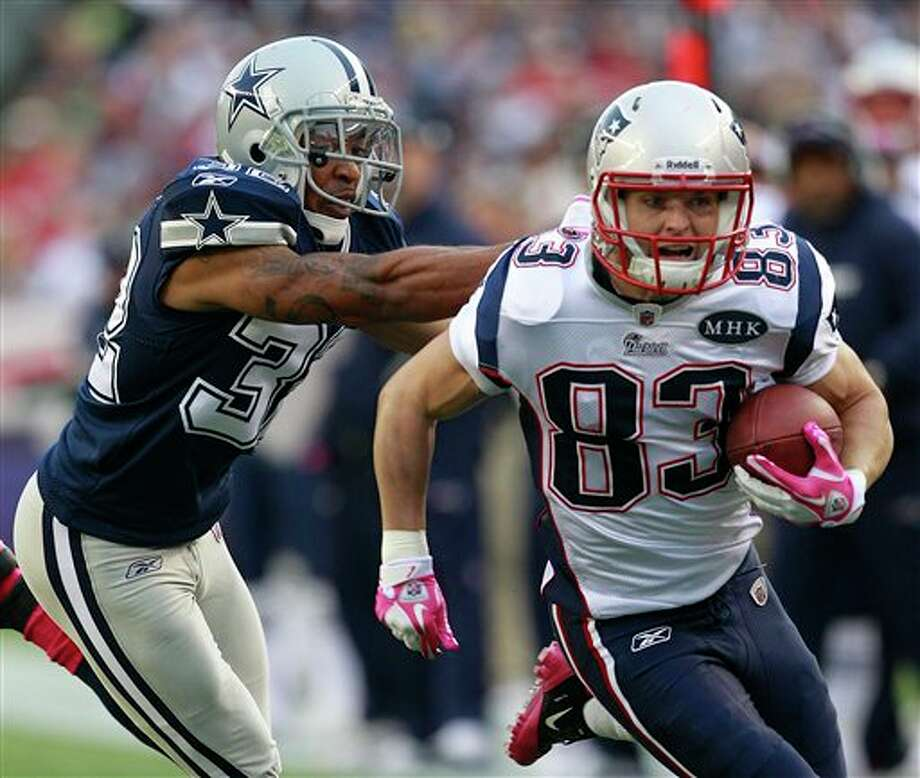 New England Patriots wide receiver Wes Welker (83) runs with pressure from Dallas Cowboys cornerback Orlando Scandrick (32) during the first quarter of an NFL  football game in Foxborough, Mass., Sunday, Oct. 16, 2011. (AP  Photo/Elise Amendola)