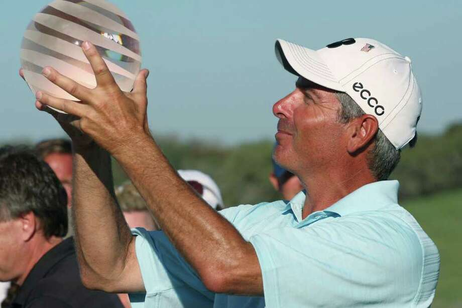 Fred Couples picks up the AT&T Championship trophy after winning the tournament with a 23-under score at the TPC San Antonio, Sunday, Oct. 16, 2011. Couples took home the $270,000 prize money. JERRY LARA/glara@express-news.net Photo: JERRY LARA, Express-News / SAN ANTONIO EXPRESS-NEWS