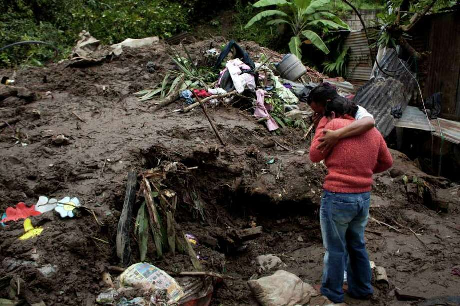 "Relatives mourn the death of five-month-old Gladys Zapeta, who died along with her grandfather and her aunt, after a landslide destroyed their home due to heavy rains in ""La Joyita"" neighborhood of Guatemala City, Sunday Oct. 16, 2011. (AP Photo/Rodrigo Abd) Photo: Rodrigo Abd"