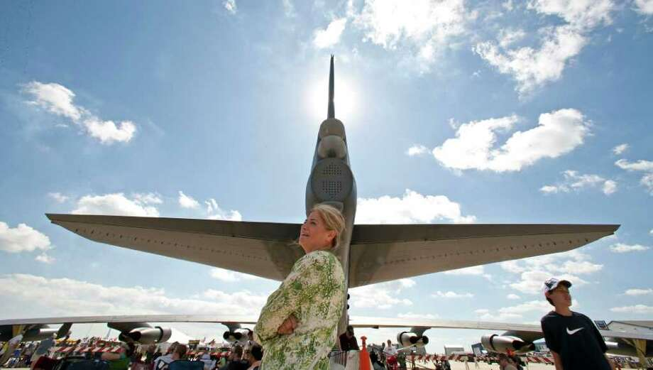 Nora Rubalcara stand in the shadow of a B-52 bomber during the 27th Annual Wings Over Houston Airshow at Ellington Airport Sunday, Oct. 16, 2011, in Houston. Photo: James Nielsen, Chronicle / © 2011 Houston Chronicle