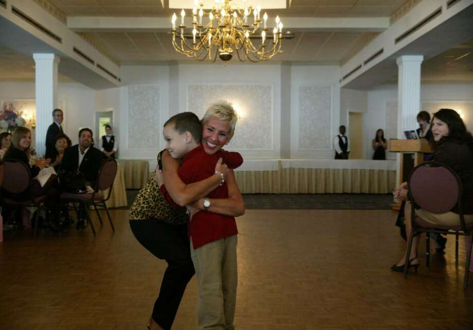 Benita Lauri of Darien gets a hug from her grandson Nicolas, while modeling  in the Breast Cancer Survival Center's tenth anniversary Celebrate Life fashion show at the Shore and Country Club in East Norwalk. Photo: Phil Noel / Connecticut Post