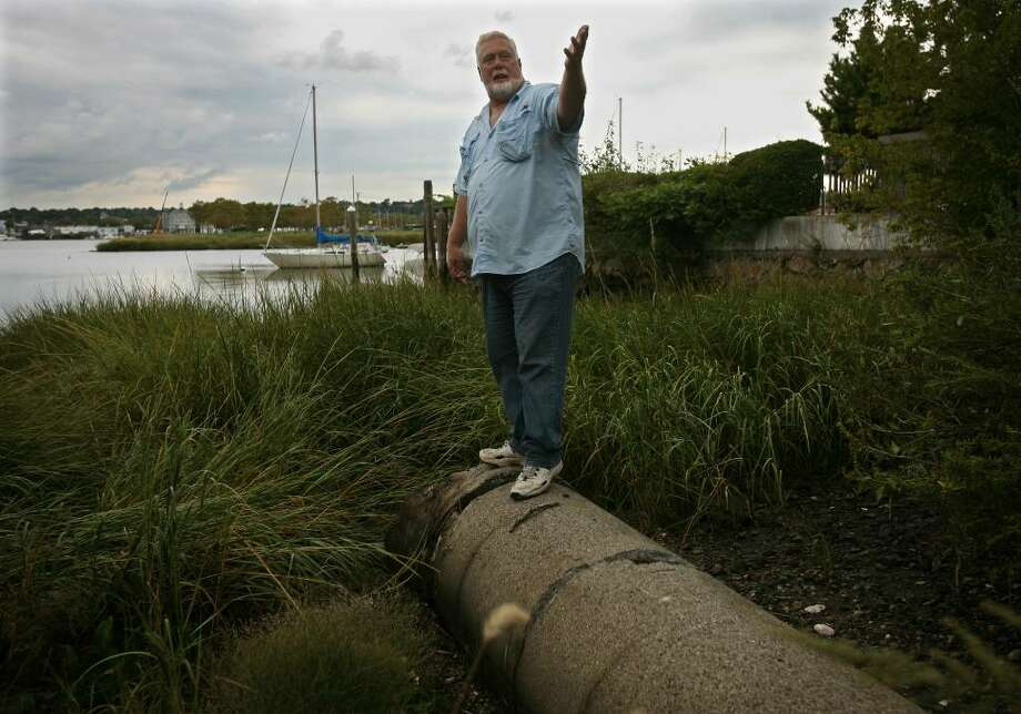 Soundkeeper Terry Backer stands on an outflow pipe that drains storm water from the Norwalk streets on Wednesday, September 16, 2009. Backer has begun a pilot program installing filters in the storm drain system to prevents oil, chemicals, heavy metals, and bacteria from washing into the Sound. Photo: Brian A. Pounds / Connecticut Post