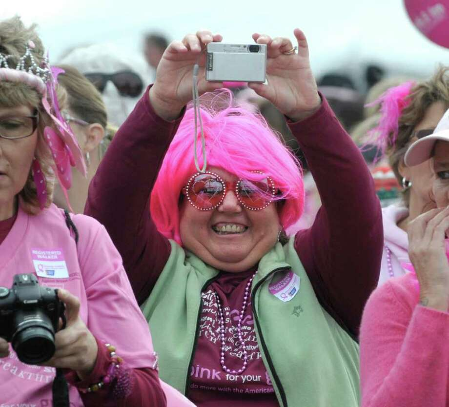 Pat Cusano from Clifton Park and an employee of Emblem Health takes a photograph with her camera during the start of Making Strides Against Breast Cancer event at Washington Park on Sunday, Oct. 16, 2011 in Albany.  (Paul Buckowski / Times Union) Photo: Paul Buckowski / 00014956A