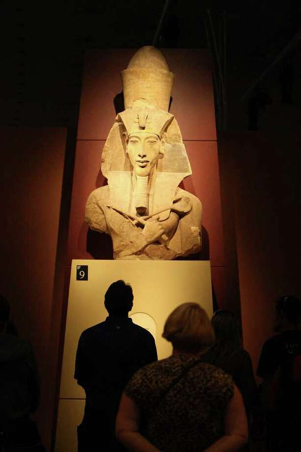 Visitors stop and look at the Colossal Statue of Amenhotep IV/Akhenaten in nemes and double crown. Photo: Karen Warren / © 2011 Houston Chronicle