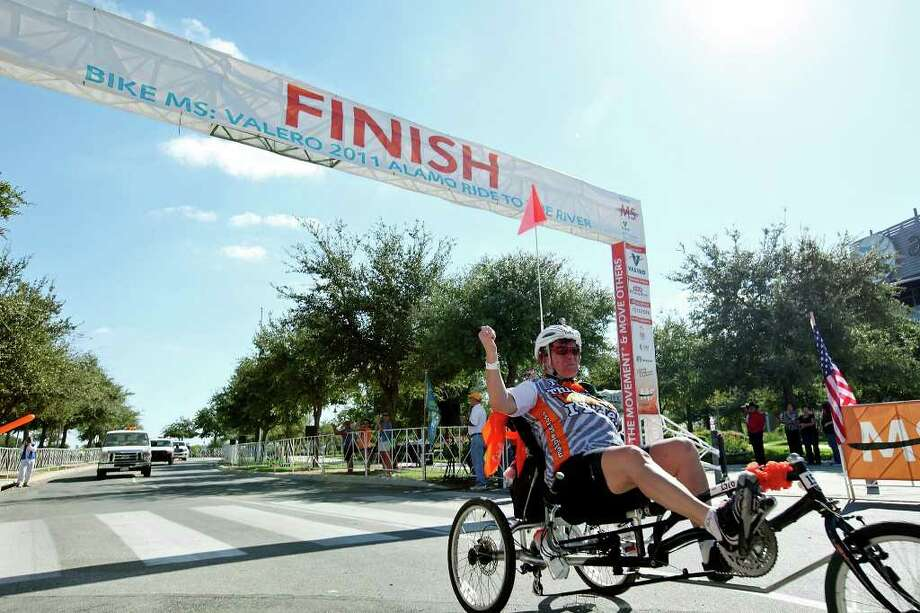 """Jodi Lee Ryan, 62 from Arlington, Tx., crosses the finish line of the Bike MS: Valero 2011 Alamo Ride to the River Sunday Oct. 16, 2011 at the AT&T Center. Ryan, who was diagnosed with multiple sclerosis in 1980, was the last cyclist to finish the ride and said after """"It was unbelievable, I feel like I won the Tour de France."""" The first day of the ride was from the AT&T Center to New Braunfels. The second day riders returned to the AT&T Center. Photo: EDWARD A. ORNELAS, EDWARD A. ORNELAS/eaornelas@express-news.net / © SAN ANTONIO EXPRESS-NEWS (NFS)"""