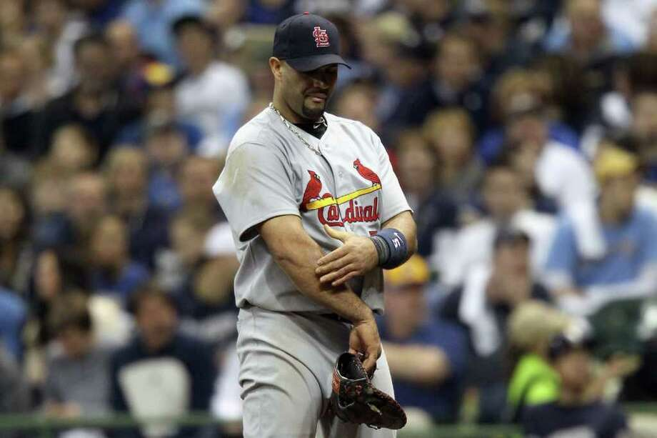 MILWAUKEE, WI - OCTOBER 16:  Albert Pujols #5 of the St. Louis Cardinals grabs his right arm after he hurt it at a play at first base against Ryan Braun #8 of the Milwaukee Brewers in the bottom of the sixth inning during Game Six of the National League Championship Series at Miller Park on October 16, 2011 in Milwaukee, Wisconsin. Photo: Christian Petersen, Getty / 2011 Getty Images