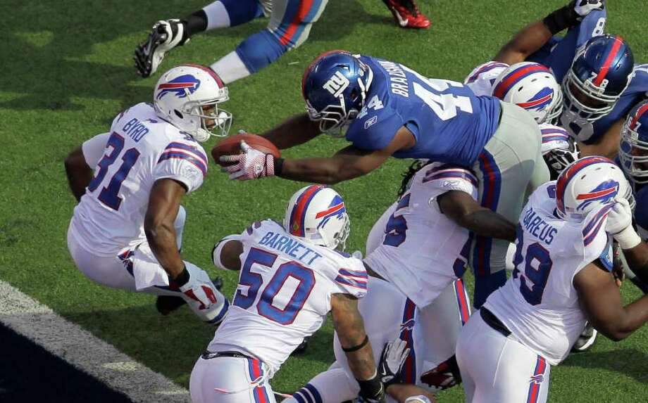New York Giants running back Ahmad Bradshaw (44) dives past Buffalo Bills free safety Jairus Byrd (31) and Nick Barnett (50) for a touchdown during the third quarter of an NFL football game on Sunday, Oct. 16, 2011, in East Rutherford, N.J.  (AP Photo/Julio Cortez) Photo: Julio Cortez