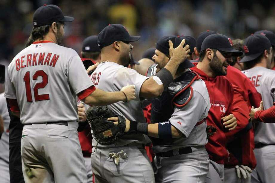 MILWAUKEE, WI - OCTOBER 16:  (L-R) Lance Berkman #12, Albert Pujols #5 and Yadier Molina #4 of the St. Louis Cardinals celebrate after they won 12-6 against the Milwaukee Brewers during Game Six of the National League Championship Series at Miller Park on October 16, 2011 in Milwaukee, Wisconsin. Photo: Jonathan Daniel, Getty / 2011 Getty Images