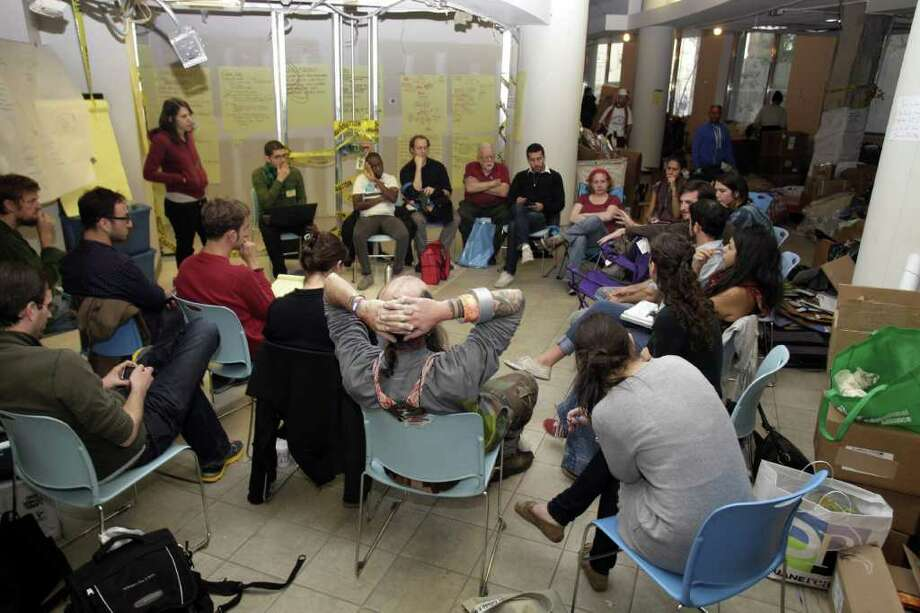 A group of activists hold a strategy meeting in a storage space for supplies supporting the camp of Occupy Wall Street protesters, Sunday, Oct.  16,  2011, in New York. The goods are housed in an unused space donated by the United Federation of Teachers. (AP Photo/David Karp) Photo: David Karp