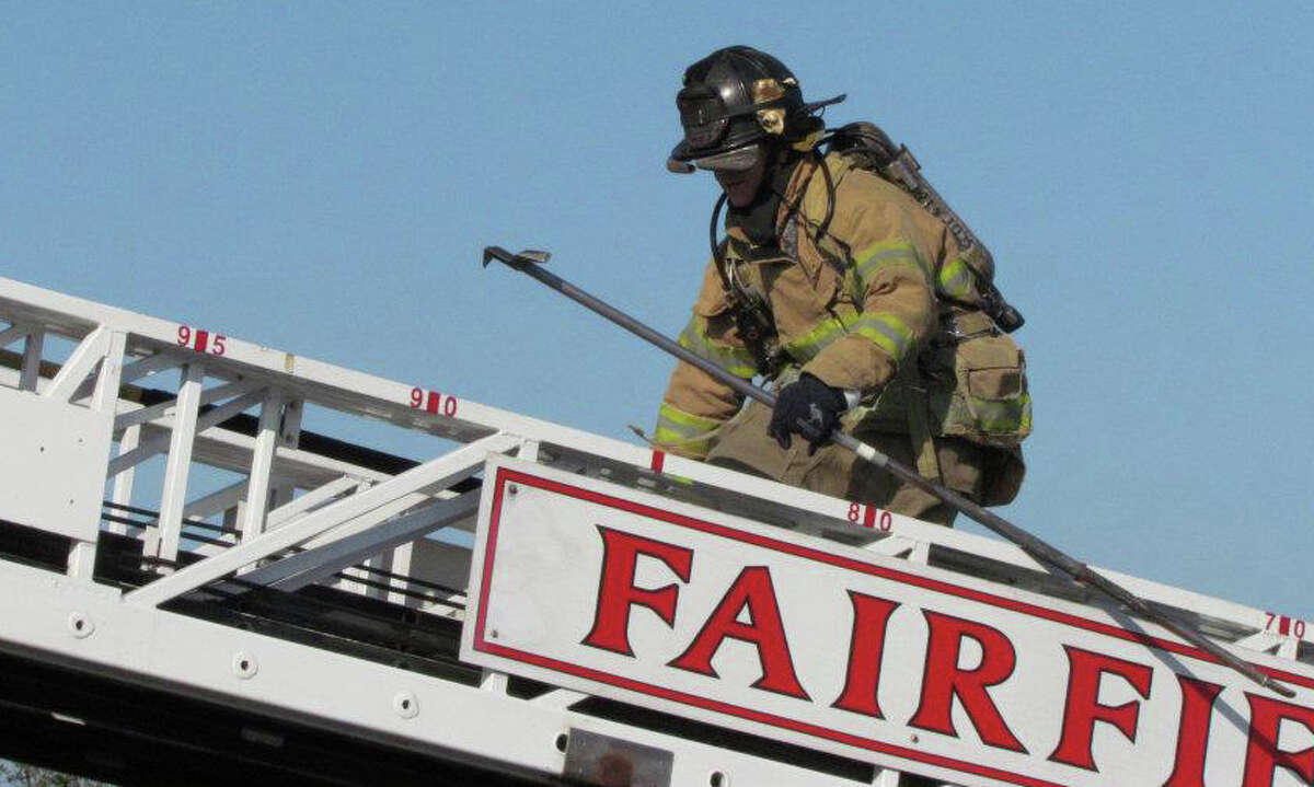 Fairfield Representative Town Meeting Moderator Jeffrey Steele navigates the Ladder 1 truck during FireOps 101 training exercise on Saturday.