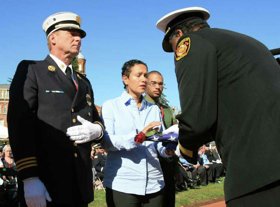 Mrianne Velasquez, wife of Bridgeport, Conn., firefighter Lt. Steve Velasquez, receives an American flag and red rose Sunday, Oct. 16, 2011 during ceremonies at the National Firefighter Trainng Academy in Emmittsburg, Md., honoring firefighters who have died during the line of duty in 2011. Flanking Velasquez are firefighters Keith Wallace, left, and her son, Aaron, 17. Eighty seven firefighters were honored during this year's ceremony. (AP Photo/Timothy Jacobsen) Photo: Timothy Jacobsen, Associated Press / Associated Press