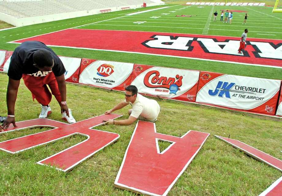 The Lamar football stadium real grass had more color added to it Friday afternoon as campus organizations came out and put their fraternities' or sorority' letters on the grassy hill in front of the Montagne Center for the opening game. Nathan Mistric, right, with Sigma Nu, helps Bobby Wilmore Jr. of Kappa Alpha Psi, position the letters for spiking so they would not move.   Dave Ryan/The Enterprise