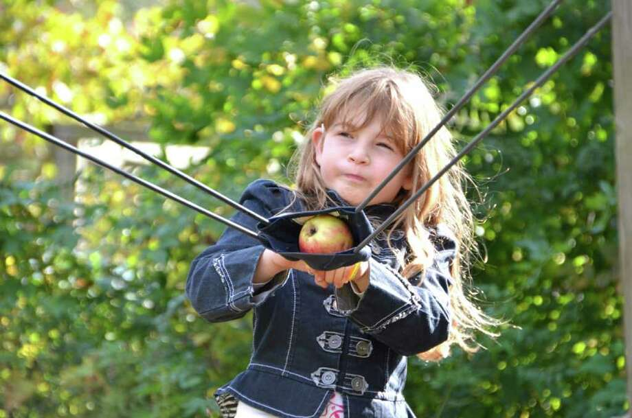 Eight-year-old Jessica Parisi pulls back the sling hoping her apple will hit the target at the New Canaan Nature Center Fall Fair. Photo: Jeanna Petersen Shepard