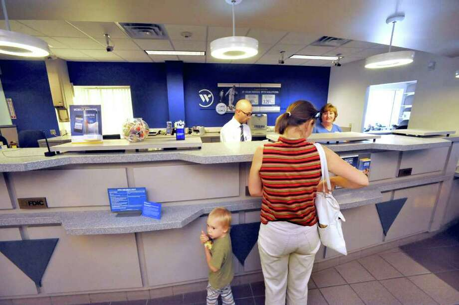 Tellers help customers in the Webster Bank branch at 83 Newtown Road in Danbury, Monday, Sept. 12, 2011. Photo: Michael Duffy / The News-Times