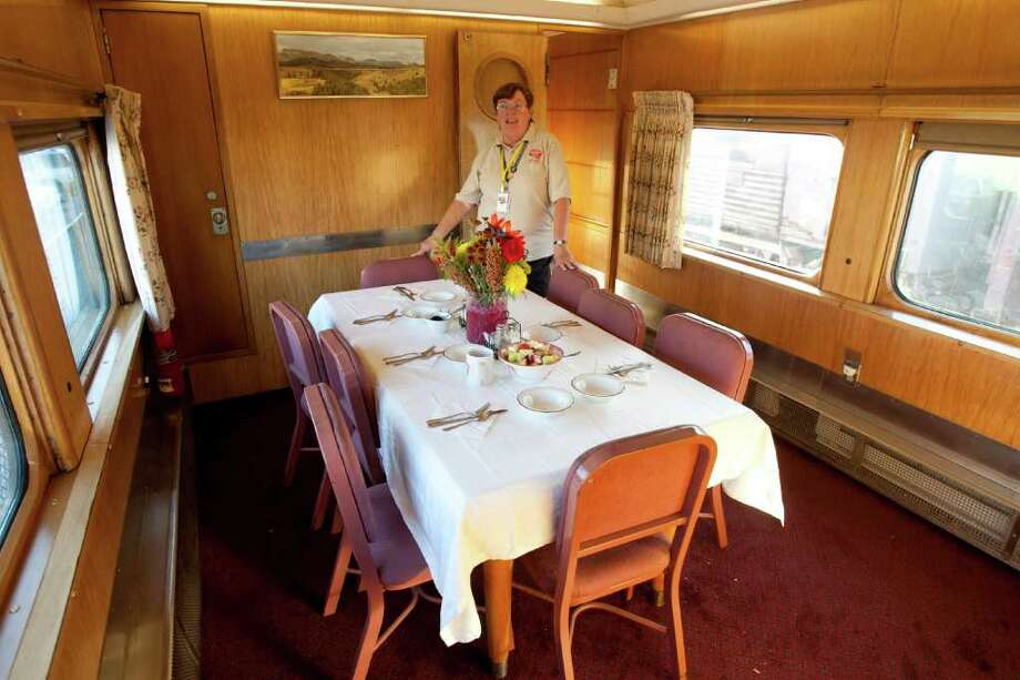Sherrie Conover talks about the Wisconsin train car dining room, one of the eighteen historic passenger train cars at the Galveston Railroad Museum Monday, Oct. 17, 2011. With various owners, the cars have a combined value of $25 million.  The train is traveling to the American Association of Private Railroad Car Owners convention in Kansas City. Photo: For To Chronicle :Thomas B. Shea