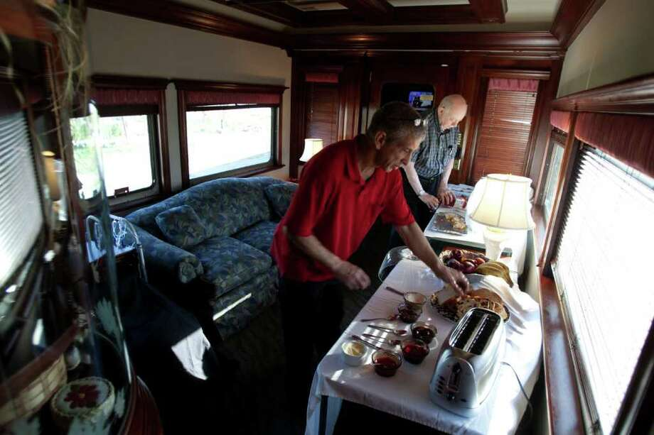 Goy Warner, left, the stewart of the Northern Sky train car makes breakfast for passenger Paul DeVerter, right, of Houston in the lounge of the Northern Sky passenger train car. The Northern Sky was built by American Car and Foundry in 1955 for the Union Pacific Railroad as number 9003. After passing into a private ownership in 1992, the interior was completely redesigned to accommodate the eight guest in four staterooms. The car's furniture and wood finish are Honduras mahogany. The car is based in Milwaukee, Wisconsin, and owned by David and Marilyn Hoffman. Photo: For To Chronicle :Thomas B. Shea