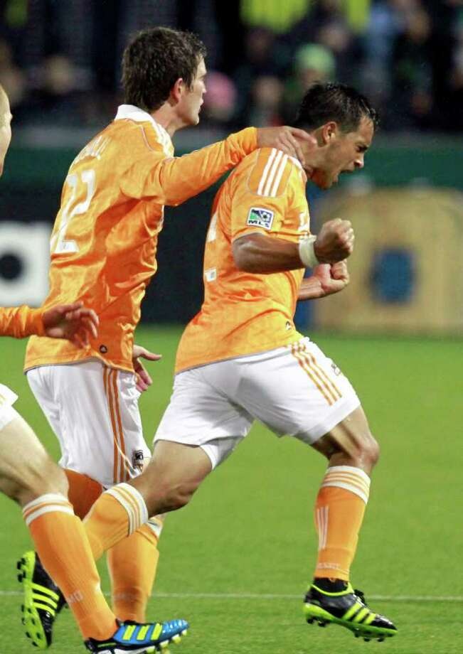 DON RYAN: ASSOCIATED PRESS ORANGE RUSH: Dynamo midfielder Danny Cruz, right, celebrates his goal with Bobby Boswell against the Timbers on Friday. Photo: Don Ryan / AP