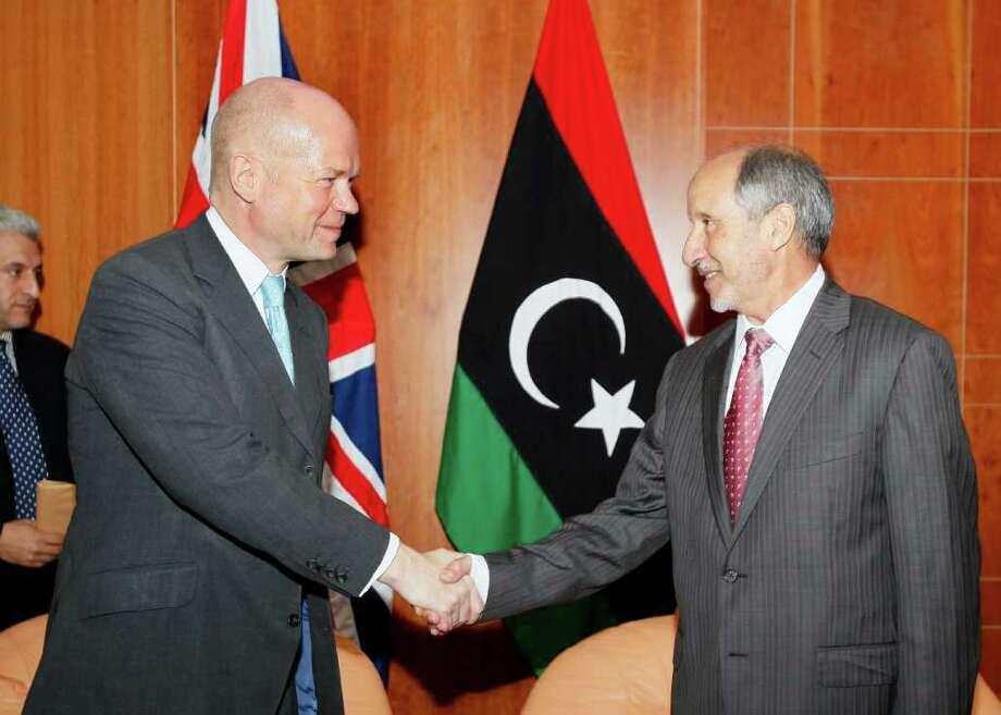 "British Foreign Secretary William Hague, left, shakes hands with Libya's interim leader Mustafa Abdul-Jalil, the head of the governing National Transitional Council in Tripoli, Libya, Monday, Oct. 17, 2011. Britain's foreign secretary says it's ""very, very important"" to catch Moammar Gadhafi and other former Libyan regime figures wanted by the International Criminal Court. William Hague made the comments Monday during a visit to Tripoli. He also promised more humanitarian aid and says the final shipment of Libyan cash that had been frozen in the United Kingdom will be returned soon. (AP Photo/Abdel Magid al-Fergany) Photo: Abdel Magid Al-Fergany / AP"
